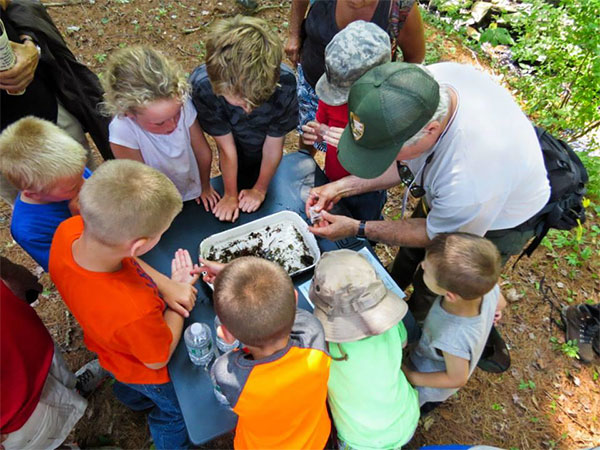 Children enjoy a lesson on aquatic insects. Photo by Roy Morsch.