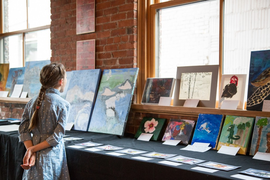 Young girl looking at the art available at the silent auction. Photo by Chris Fischer.